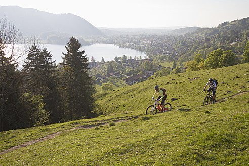 Germany, Bavaria, Schliersee, Man and woman moutainbiking on mountains - FFF001198
