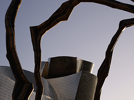 Spain, Basque country, Bilbao, View of Guggenheim Museum Bilbao with sculpture in background at dusk - BSC000010