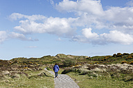 United Kingdom, Northern Ireland, County Down, Newcastle, Mourne Mountains,  Murlough National Nature Reserve, Person walking away near dunes - SIEF001605
