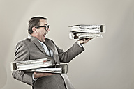 Close up of mature businessman at office holding stack of file - MAEF003437