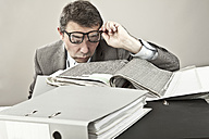 Close up of mature businessman at office with files and removing spectacles - MAEF003440