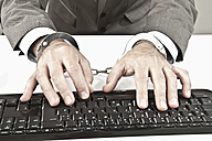 Close up of businessman's hand cuffed while cyber crime - MAEF003449