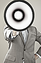 Close up of businessman with face covered with megaphone against grey background - MAEF003466