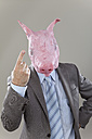 Close up of businessman with pigs head in office against grey background - MAEF003473