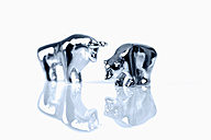 Close up of bear and bull figurine with reflection on white background - TSF000313