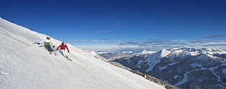 Austria, Salzburg Country, Altenmarkt-Zauchensee, Mid adult couple skiing on ski slope in winter - HHF003736