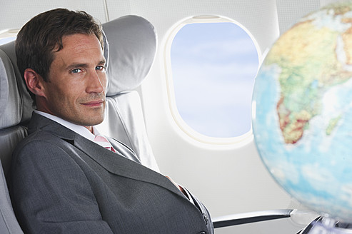 Germany, Bavaria, Munich, Mid adult businessman looking at globe in business class airplane cabin - WESTF016792