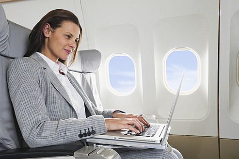 Germany, Bavaria, Munich, Mid adult businesswoman using laptop in business class airplane cabin - WESTF016795