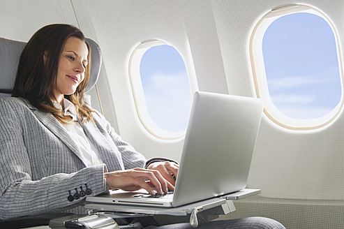 Germany, Bavaria, Munich, Mid adult businesswoman using laptop in business class airplane cabin - WESTF016801