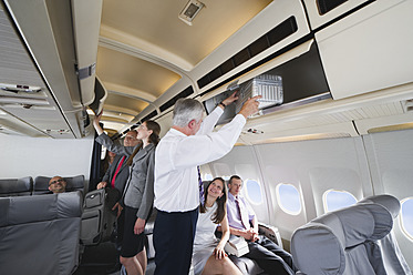Germany, Bavaria, Munich, Passengers removing hand luggage from shelf in business class airplane cabin - WESTF016867