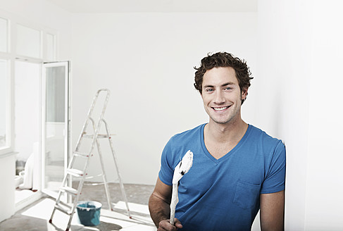 Germany, Cologne, Close up of young man holding paint brush in renovating apartment, smiling, portrait - FMKF000326