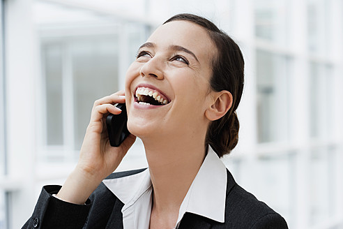 Germany, Bavaria, Diessen am Ammersee, Young businesswoman talking on mobile phone, laughing, close up - JRF000283