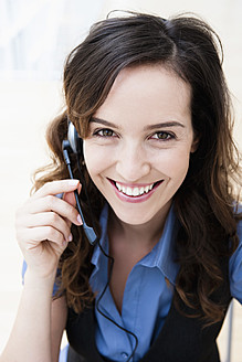 Germany, Bavaria, Diessen am Ammersee, Young businesswoman using headset, smiling, portrait - JRF000293
