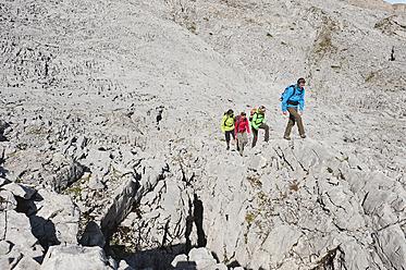 Austria, Kleinwalsertal, Group of people hiking on rocky mountain trail - MIRF000217