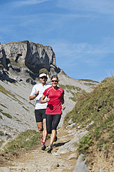 Austria, Kleinwalsertal, Man and woman running on mountain trail - MIRF000229