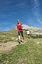 Austria, Kleinwalsertal, Man and woman running on mountain trail - MIRF000232