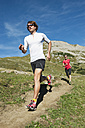 Austria, Kleinwalsertal, Man and woman running on mountain trail - MIRF000235