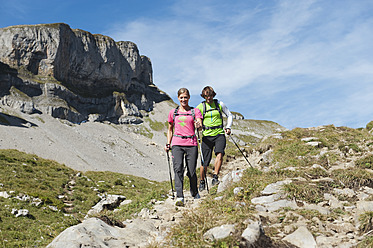 Austria, Kleinwalsertal, Man and woman hiking on mountain trail - MIRF000238