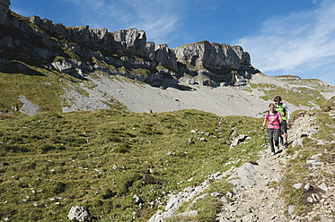 Austria, Kleinwalsertal, Man and woman hiking on mountain trail - MIRF000241