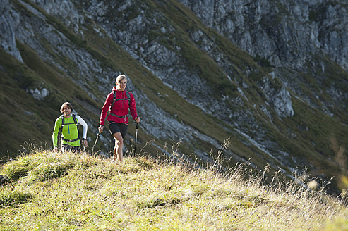 Austria, Kleinwalsertal, Man and woman hiking on mountain trail - MIRF000247
