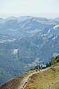 Austria, Kleinwalsertal, Man and woman hiking on mountain trail - MIRF000250