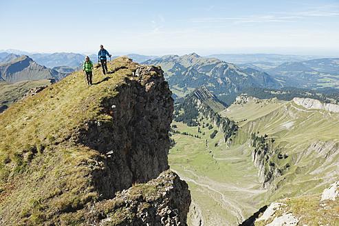 Austria, Kleinwalsertal, Man and woman hiking on edge of cliff - MIRF000253