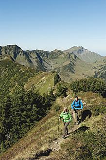 Austria, Kleinwalsertal, Man and woman hiking on mountain trail - MIRF000256