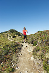 Austria, Kleinwalsertal, Mid adult man running on mountain trail - MIRF000259