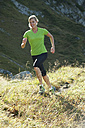 Austria, Kleinwalsertal, Young woman running on mountain trail - MIRF000271