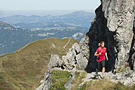 Austria, Kleinwalsertal, Young woman running on mountain trail near rocks - MIRF000274