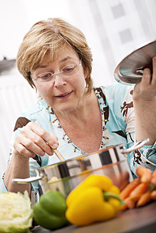 Close up of mature woman cooking fresh vegetables in pot - TSF000310