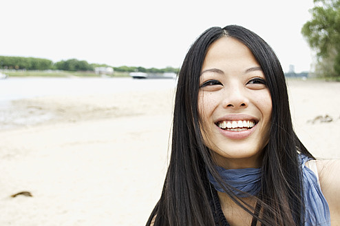 Germany, Close up of young woman at Rhine riverside, portrait, smiling - LFO000096
