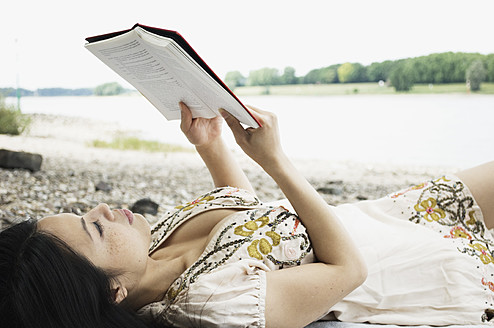 Germany, Young woman lying and reading book at Rhine riverside - LFO000105