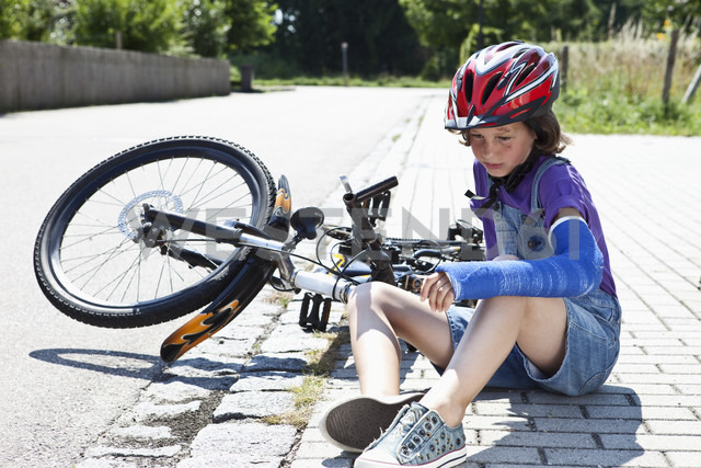 Germany, Bavaria, Wounded girl sitting on road after bicycle accident - MAEF003573 - Roman Märzinger/Westend61