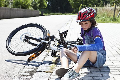 Germany, Bavaria, Wounded girl sitting on road after bicycle accident - MAEF003573