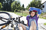 Germany, Bavaria, Wounded girl sitting on road after bicycle accident - MAEF003574