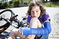 Germany, Bavaria, Wounded girl sitting on road after bicycle accident - MAEF003575