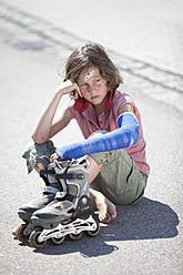Germany, Bavaria, Wounded girl sitting on road after inline-skating accident - MAEF003578