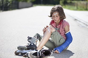 Germany, Bavaria, Wounded girl sitting on road after inline-skating accident - MAEF003582