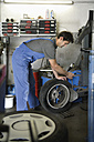Germany, Ebenhausen, Mechatronic technician working on tyre in car garage - TCF001617
