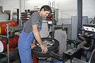 Germany, Ebenhausen, Mechatronic technician working on tyre in car garage - TCF001619
