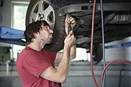Germany, Ebenhausen, Mechatronic technician working in car garage - TCF001628