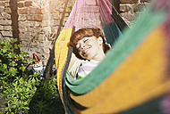 Germany, Berlin, Young woman in hammock, smiling - WESTF016903