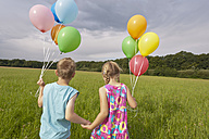 Germany, North Rhine-Westphalia, Hennef, Girl and boy holding balloons and walking in meadow - KJF000129