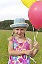 Germany, North Rhine-Westphalia, Hennef, Girl holding balloons and standing in meadow - KJF000130