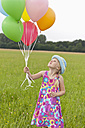 Germany, North Rhine-Westphalia, Hennef, Girl holding balloons and standing in meadow - KJF000131