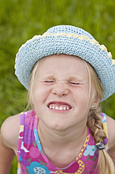 Germany, North Rhine-Westphalia, Hennef, Girl with tightly closed eyes wearing sun hat, close up - KJF000132