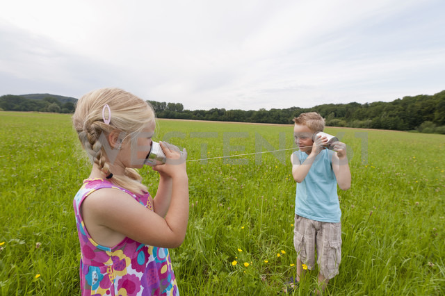 Germany, North Rhine-Westphalia, Hennef, Boy and girl in meadow playing with tin can phone - KJF000135