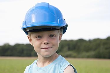 Germany, North Rhine-Westphalia, Hennef, Boy with construction worker helmet standing in meadow, portrait, close up - KJF000138