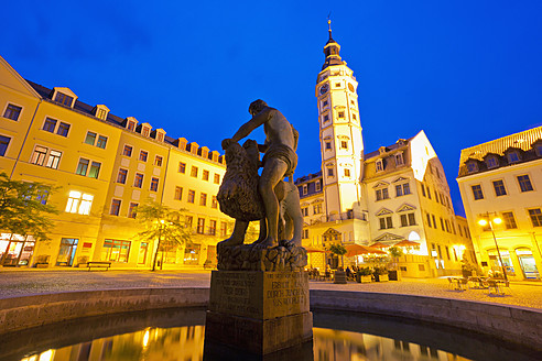 Germany, Thuringia, Gera, View of Simsonbrunnen fountain, town hall, beer tavern and restaurant at dusk - WD001017